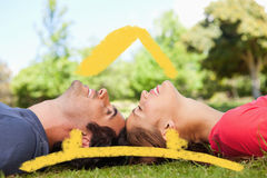 Composite image of two smiling friends with their eyes closed while lying head to head Royalty Free Stock Photography