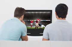 Composite image of two soccer fans watching tv Royalty Free Stock Photo