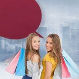 Composite image of two young women with shopping bags with speech bubble Royalty Free Stock Photo