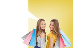 Composite image of two young women with shopping bags with speech bubble Stock Image