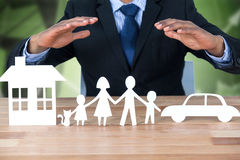 Composite image of underwriter protecting family in paper with his hands Stock Image