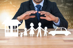 Composite image of underwriter protecting family in paper with his hands Stock Images