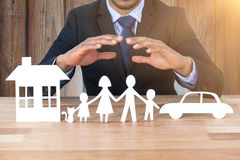 Composite image of underwriter protecting family in paper with his hands Royalty Free Stock Photo
