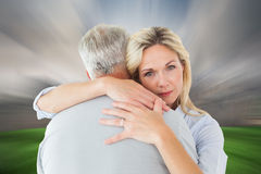 Composite image of unhappy blonde hugging her husband Royalty Free Stock Photos
