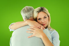 Composite image of unhappy blonde hugging her husband Stock Photos