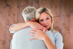 Composite image of unhappy blonde hugging her husband Stock Photo