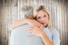 Composite image of unhappy blonde hugging her husband Stock Images