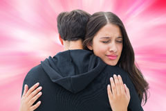 Composite image of unhappy brunette hugging her boyfriend Stock Image