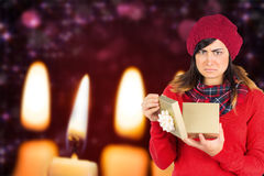 Composite image of unhappy brunette opening christmas gift Royalty Free Stock Images
