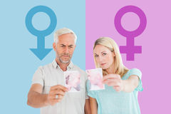 Composite image of unhappy couple holding two halves of torn photograph Stock Image