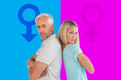 Composite image of unhappy couple not speaking to each other. Unhappy couple not speaking to each other  against pink and blue Stock Image