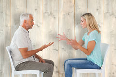 Composite image of unhappy couple sitting on chairs having an argument. Unhappy couple sitting on chairs having an argument against pale wooden planks Stock Images