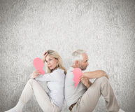Composite image of unhappy couple sitting holding two halves of broken heart. Unhappy couple sitting holding two halves of broken heart against weathered surface Royalty Free Stock Photos