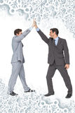 Composite image of unified business team high fiving each other. Unified business team high fiving each other against snowflakes on silver Stock Photography