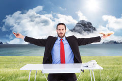 Composite image of unsmiling businessman sitting with arms outstretched. Unsmiling businessman sitting with arms outstretched against scenic backdrop Royalty Free Stock Photography