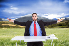 Composite image of unsmiling businessman sitting with arms outstretched. Unsmiling businessman sitting with arms outstretched against scenic backdrop Stock Photos