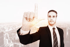 Composite image of unsmiling businessman in suit pointing up his finger. Unsmiling businessman in suit pointing up his finger against new york Royalty Free Stock Image