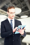 Composite image of unsmiling businessman using tablet pc Royalty Free Stock Photo