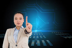 Composite image of unsmiling businesswoman pointing Stock Image