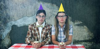 Composite image of unsmiling geeky hipsters celebrating birthday. Unsmiling geeky hipsters celebrating birthday  against rusty weathered wall Stock Images
