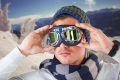Composite image of unsmiling man wearing aviator goggles. Unsmiling man wearing aviator goggles against snow covered tree on ski slope stock photos