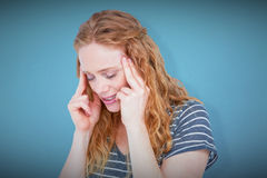 Composite image of upset blonde woman suffering from headache. Upset blonde woman suffering from headache against blue background Stock Images