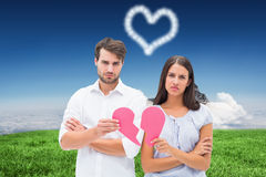Composite image of upset couple holding two halves of broken heart Royalty Free Stock Image