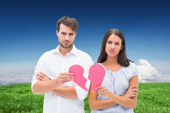 Composite image of upset couple holding two halves of broken heart Royalty Free Stock Photos