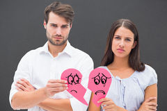 Composite image of upset couple holding two halves of broken heart Royalty Free Stock Photo