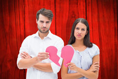 Composite image of upset couple holding two halves of broken heart Stock Photo