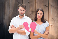 Composite image of upset couple holding two halves of broken heart Stock Photography