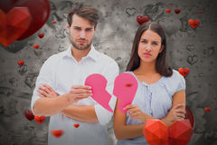 Composite image of upset couple holding two halves of broken heart 3D. Upset couple holding two halves of broken heart against love heart pattern 3D Royalty Free Stock Photos