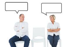 Composite image of upset couple not talking to each other after fight. Upset couple not talking to each other after fight against speech bubble Royalty Free Stock Image