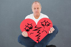 Composite image of upset man sitting holding heart shape Royalty Free Stock Photography