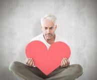 Composite image of upset man sitting holding heart shape Royalty Free Stock Photos