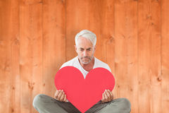 Composite image of upset man sitting holding heart shape Stock Photography