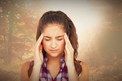 Composite image of upset woman suffering from headache Royalty Free Stock Image