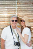 Composite image of vacationing couple. Vacationing couple against wooden background in pale wood Royalty Free Stock Photography