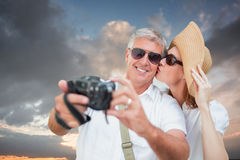 Composite image of vacationing couple taking photo. Vacationing couple taking photo against blue and orange sky with clouds Royalty Free Stock Photography