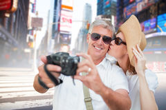 Composite image of vacationing couple taking photo. Vacationing couple taking photo against blurry new york street Stock Photo