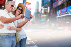 Composite image of vacationing couple taking photo Stock Photography