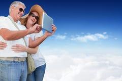 Composite image of vacationing couple taking photo Stock Image