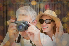 Composite image of vacationing couple taking photo. Vacationing couple taking photo against close up of christmas lights Stock Image