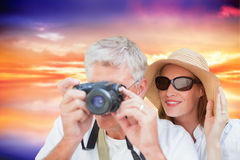 Composite image of vacationing couple taking photo. Vacationing couple taking photo against purple sky with orange clouds Royalty Free Stock Photos