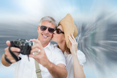 Composite image of vacationing couple taking photo. Vacationing couple taking photo against room with large window looking on city Royalty Free Stock Photos