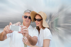 Composite image of vacationing couple taking photo. Vacationing couple taking photo against room with large window looking on city Stock Photography