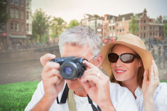 Composite image of vacationing couple taking photo. Vacationing couple taking photo against sunny day in amsterdam Stock Photo