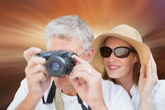 Composite image of vacationing couple taking photo. Vacationing couple taking photo against sunrise over mountains Royalty Free Stock Photo