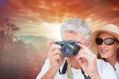 Composite image of vacationing couple taking photo. Vacationing couple taking photo against sunrise over mountains Royalty Free Stock Photography