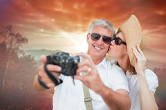 Composite image of vacationing couple taking photo. Vacationing couple taking photo against sunrise over mountains Stock Photo